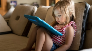 Young girl with ipad sitting on the couch