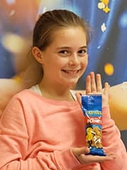 Grace holding a packet of peanuts