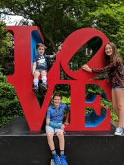 family standing smiling on LOVE statue