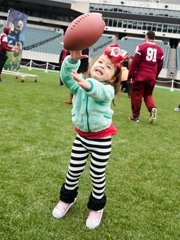 Young girl catching a football
