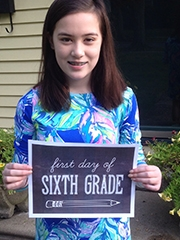 Kate holding up a 6th grade school poster