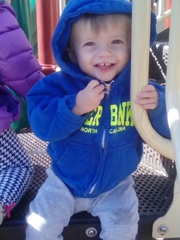 Tristan sitting at a playground smiling