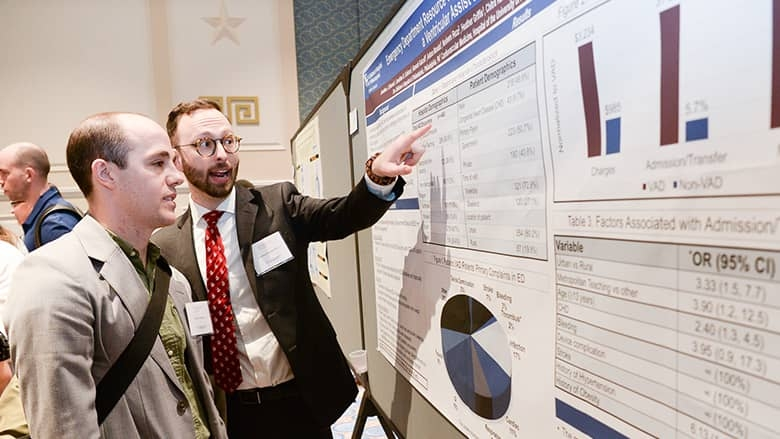 Cardiology 2020 presenter pointing to research poster