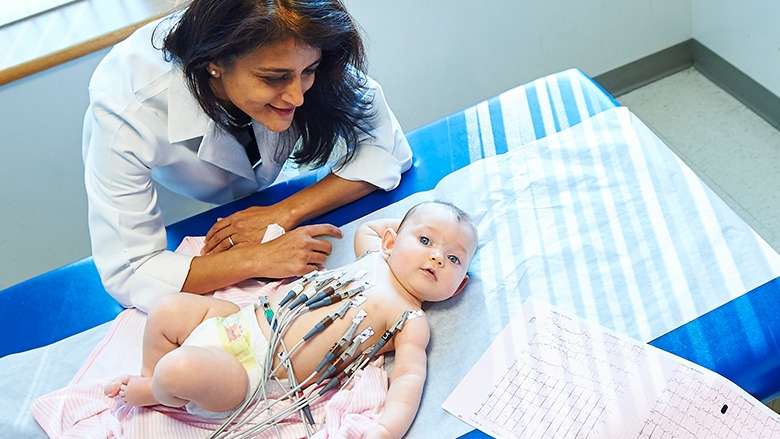 Doctor observing baby with ECG leads connected