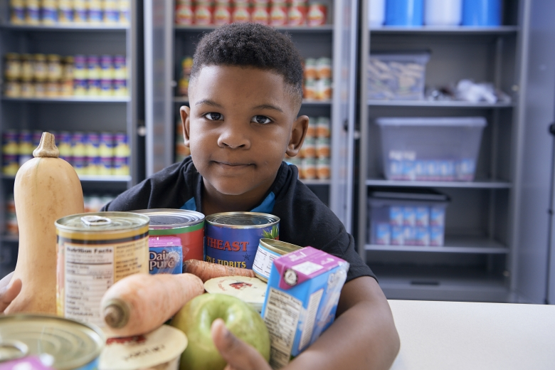 boy holding canned goods at food pharmacy
