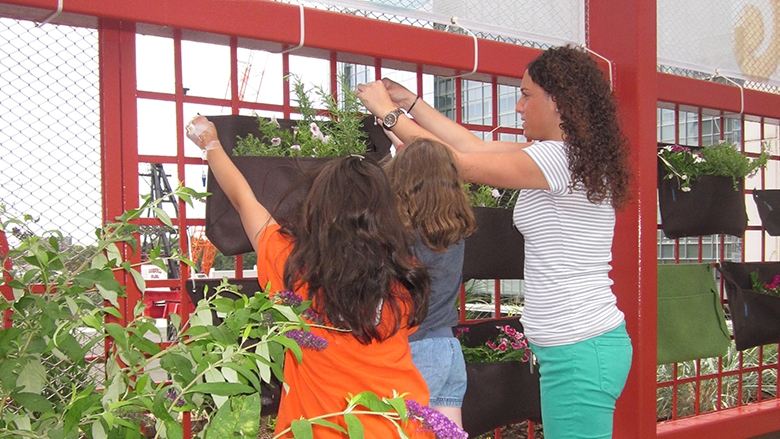Natalie Virgilio of Child Life helps Jaritza Olavarria, 12, and Maci McAnnaney, 9, hang their Wooly Pockets on the wall of the Sea Garden.