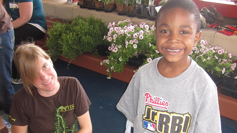 Nathaniel Hardy, 5, takes a break from his work with a volunteer from the Pennsylvania Horticultural Society to smile for the camera.