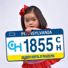Young girl holding sample CHOP license plate