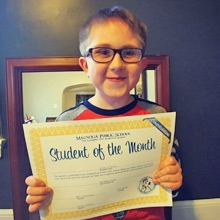 Riley holding Student of the Month award