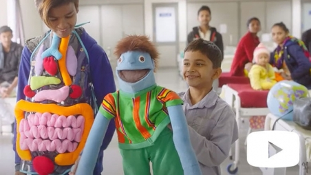 Woman in human body organ costume and boy with puppet