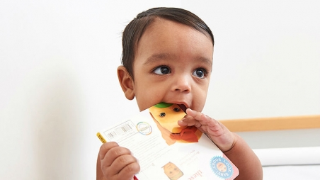 Toddler with book in his mouth
