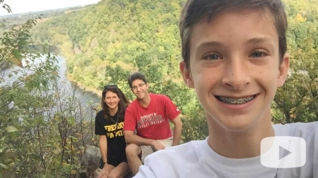 Connor selfie with parents and wooded valley behind him