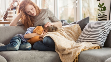 Mother laying on couch comforting sick child
