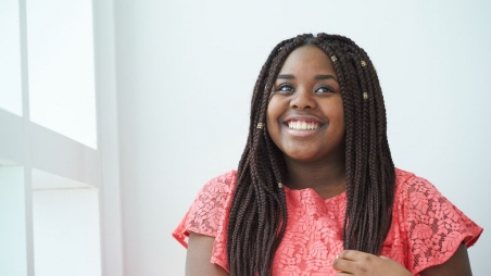 girl with braids in red shirt smiling