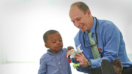 Doctor with patient playing with finger puppets
