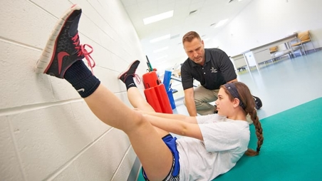 Teen doing stretches during physical therapy