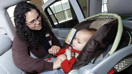 mother strapping baby in carseat