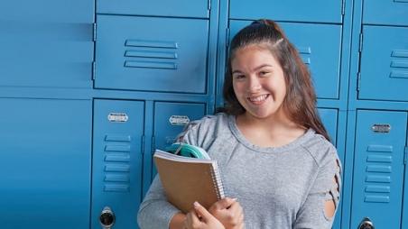 Teenage girl in school by her locker