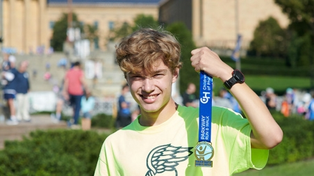 Parkway run participant holding his medal