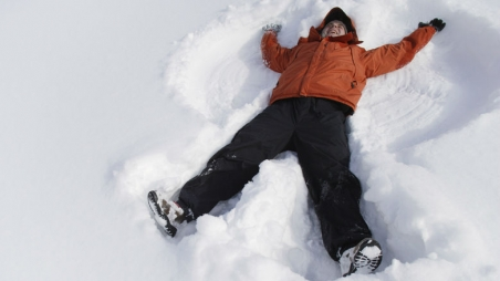 Young child making a snow angel