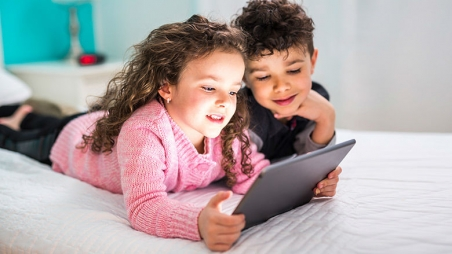 Two children using a mobile tablet