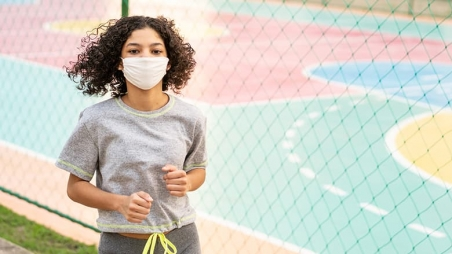 Teen athlete jogging outside wearing a protective mask