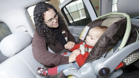 Mom buckling baby into car seat