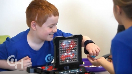Boy playing Battleship game with woman