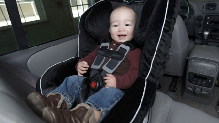 Smiling baby in rear facing car seat