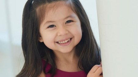 young girl patient leaning against wall smiling