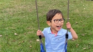 Olly riding a swing