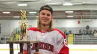 Jared holding his hockey trophy