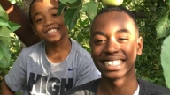 Emerson and Kenny outside under apple tree