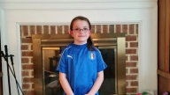 Emma wearing a soccer jersey smiling standing in front of a fireplace