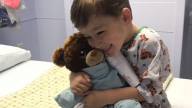 boy holding stuffed animal on hospital bed