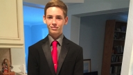 Luke in a suit standing at home