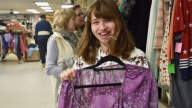 Cerebral palsy patient in thrift store holding purple shirt