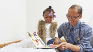Doctor reading a book to his young patient
