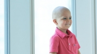 Young boy cancer patient sitting in hospital window smiling