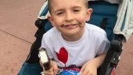 little boy GI patient in stroller eating ice cream bar