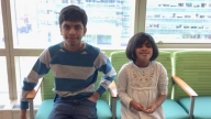 Yusuf and Khadija smiling sitting on chairs together