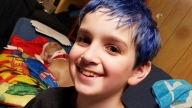 Zak with blue hair smiling