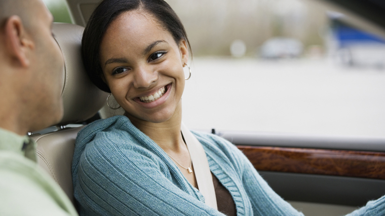 Teen girl driver in car smiling at father
