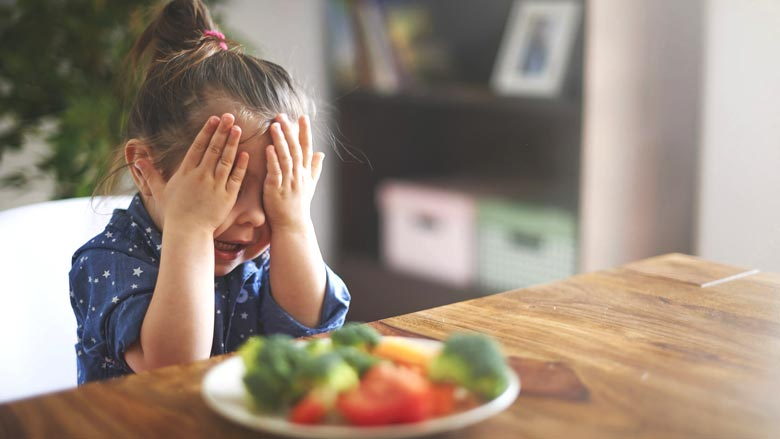 Young girl with hands over eyes sitting in front of a plate of food