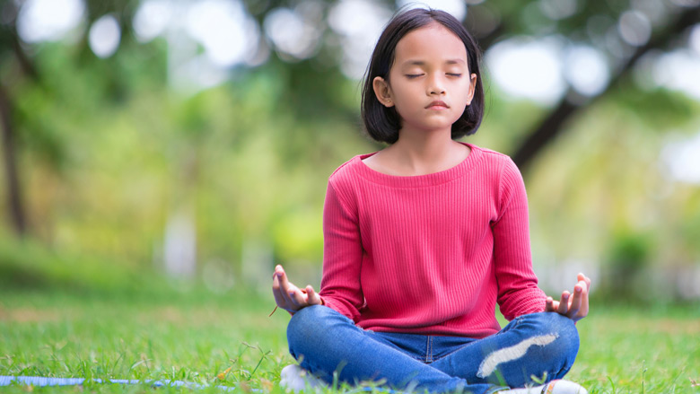 Young girl meditating outside
